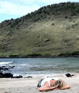 Me laying on the beach with a book at Halawa Bay on the East End of Molokai.